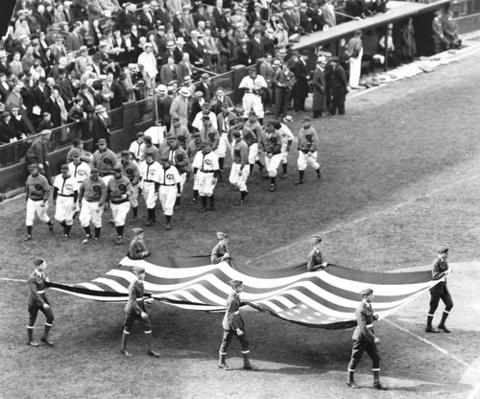 The Chicago Cubs marched behind the American flag for opening day festivities in 1933.