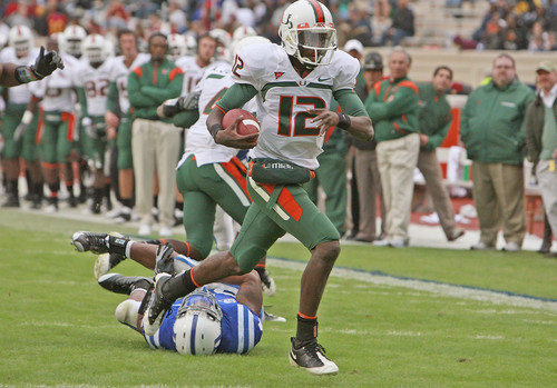 Miami's Jacory Harris (12) slips past Duke defender Michael Tauiliili to score on a 15-yard run.