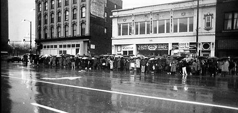 Commuters at the corner of Division Street and Milwaukee Avenue wait for CTA shuttle buses. Flood waters forced the closure of the Dearborn Street and State Street subways.