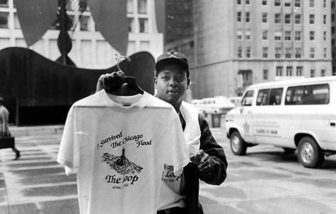 """Street vendor Matthew Cooper sells """"I Survived the Great Chicago Flood"""" t-shirts in the Daley Plaza on April 14, 1992."""