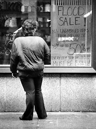 A passerby looks at a flood sale sign in a hand bag store at Wabash and Randolph Streets. Items in numerous downtown Chicago basements and sub-basements were damaged or destroyed due to the Great Chicago Flood.