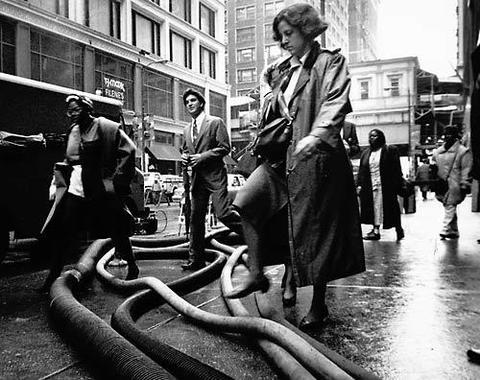 Pedestrians step over hoses used to pump out flood water from buildings at the intersection of State and Madison Streets. Scenes like this on downtown Chicago streets were commonplace in April 1992, due to massive basement and sub-basement flooding caused when crews punctured a century-old freight tunnel located underneath the Chicago River.