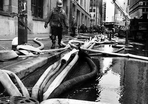 Hoses used to pump flood water out of the basement in Chicago City Hall are routed into a sewer.