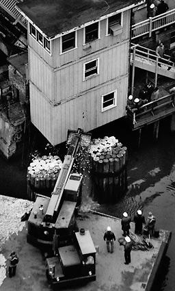 City workers and officials stand by as a crane pours gravel into the Chicago River near the Kinzie Street Bridge in an attempt to plug a hole in a freight tunnel that runs under the river. By some accounts, the hole was 20 feet wide. It took days before the Kenny Construction company was able to control the leak by drilling shafts into the tunnel where the flood had begun and placing emergency plugs inside.