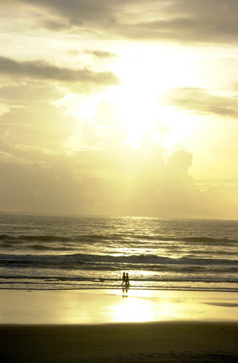 A couple takes a stroll along New Smyrna Beach at sunrise.