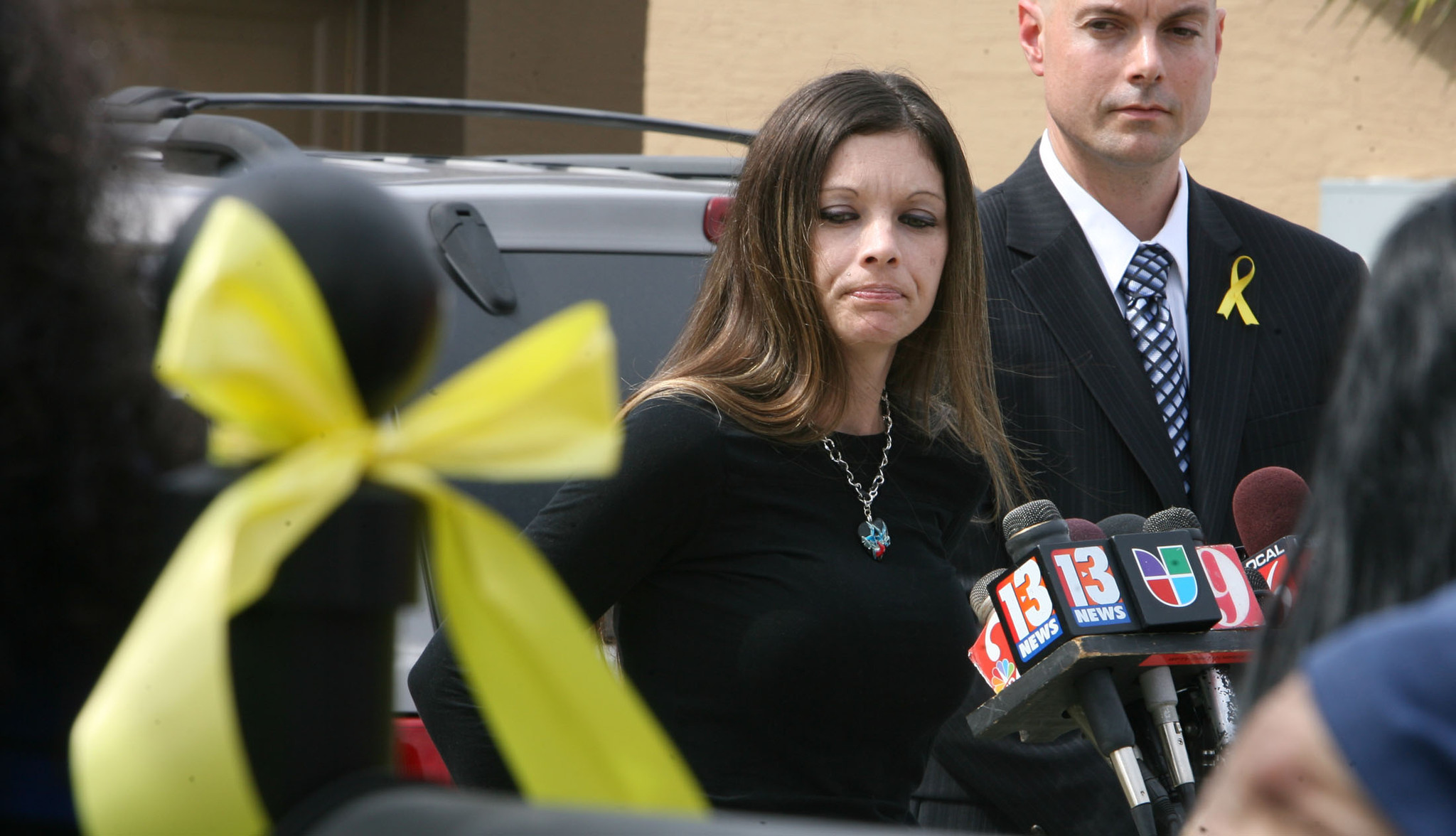 Tanya Perdomo, wife of missing firefighter Jerry Perdomo talks to the media as a yellow ribbon hangs from their mailbox at their family home.  Dave Williams, firefighter union representative stands by her side.