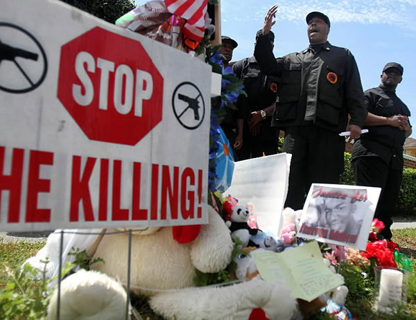 Mikhail Muhammad, center, leads a protest by the New Black Panther Party on Saturday, March 24, 2012, in front of the Retreat at Twin Lakes community in Sanford, Florida, where Trayvon Martin was shot and killed last month.
