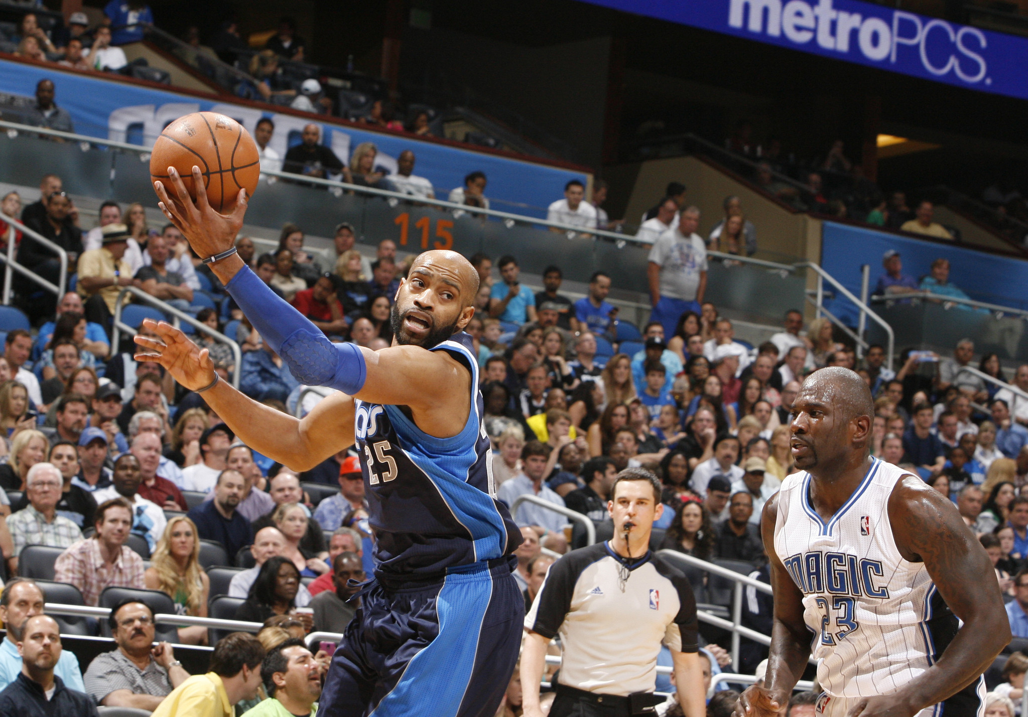 Dallas guard Vince Carter (25) grabs a rebound away from Orlando guard Jason Richardson (23) during the Mavericks' 98-100 victory over the Magic in Orlando, Fla. Friday, March 30, 2012.