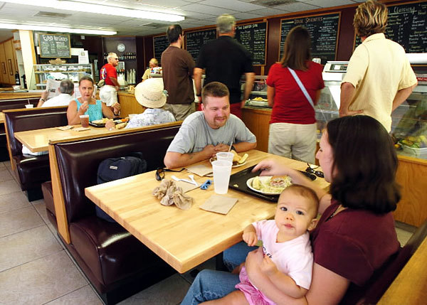 Stephen Davis of Oviedo sits with wife, Sherri, and daughter Colleen at Brandywine's Deli on Wednesday, July 6, 2005. After 40 years, the deli on Winter Park's Park Avenue will close its doors this spring.