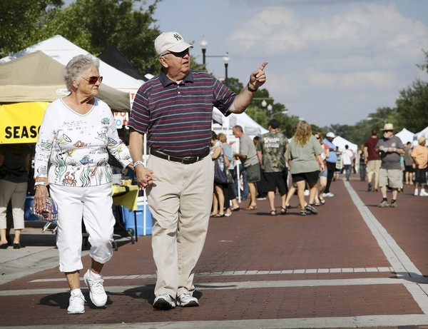 Andy Andrusko and girlfriend Peggy Sharp, both from Sanford, stroll down First Street during the Alive After 5 event in downtown Sanford on April 12, 2012.
