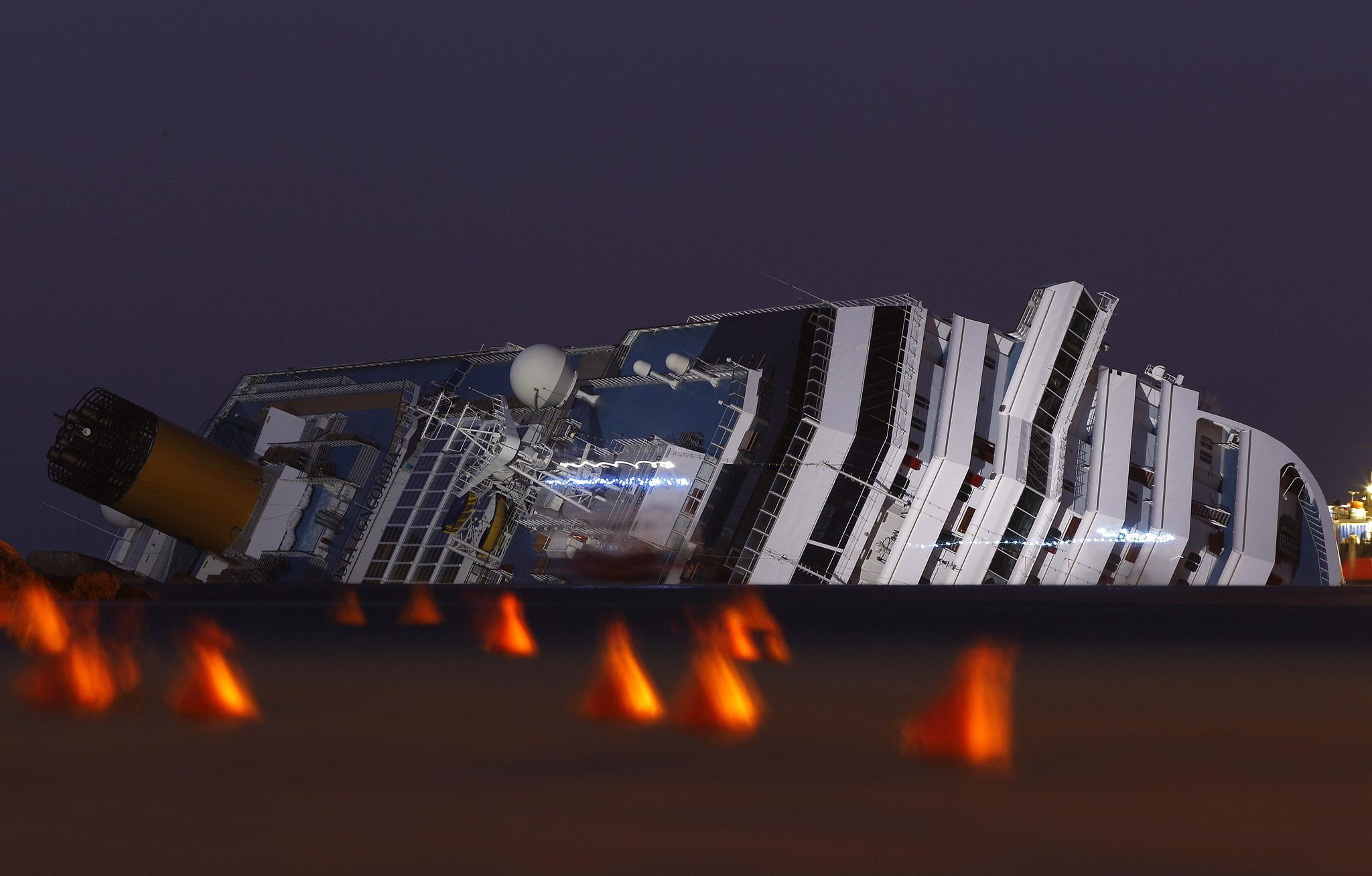 The Costa Concordia cruise ship which ran aground off the west coast of Italy at Giglio island lies on its side, half-submerged and threatening to slide into deeper waters.