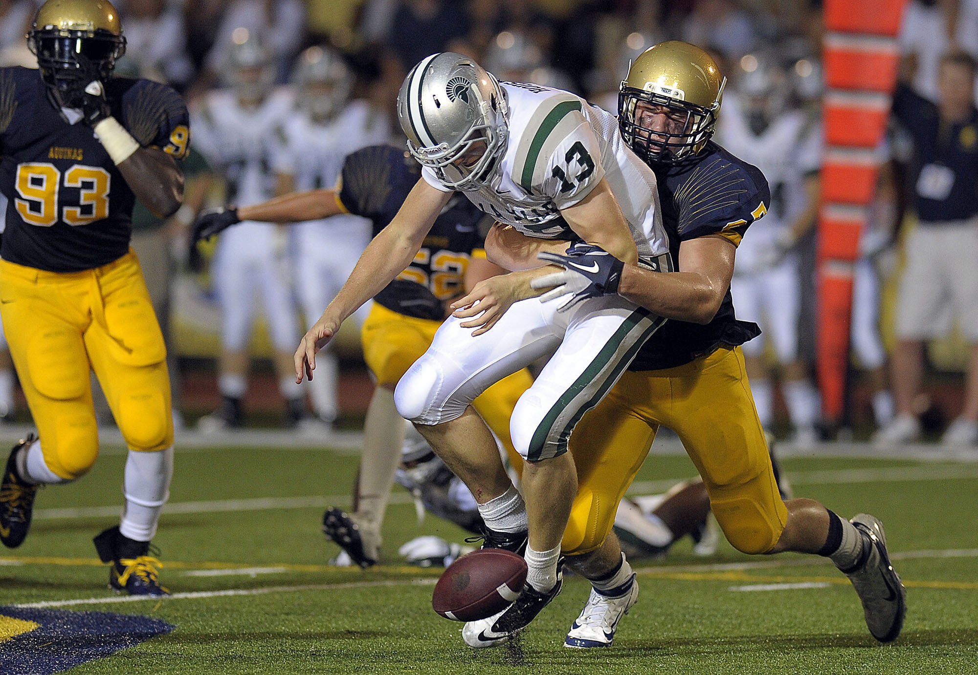 St. Thomas Aquinas lineman Joseph Bosa strips the ball loose from De La Salle quarterback Bart Houston.