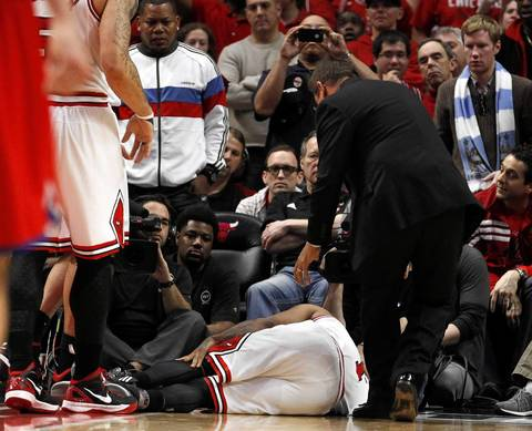 Chicago Bulls point guard Derrick Rose (1) holds his knee as Chicago Bulls head athletic trainer Fred Tedeschi rushes over to attend to him.
