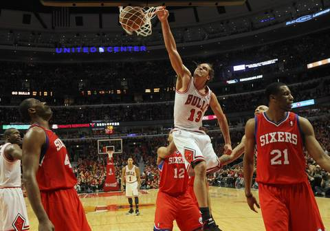 Chicago Bulls center Joakim Noah (13) goes high as he dunks in front of Philadelphia 76ers shooting guard Evan Turner (12) while Philadelphia's forward Elton Brand (42) watches.