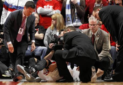 Chicago Bulls point guard Derrick Rose (1) is helped by Chicago Bulls head athletic trainer Fred Tedeschi after he was injured late in the game.