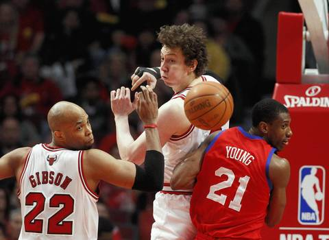 Chicago Bulls forward Taj Gibson (22), left, Bulls center Omer Asik (3), and Philadelphia 76ers forward Thaddeus Young (21) eye the ball as it bounces away from them during the first half.