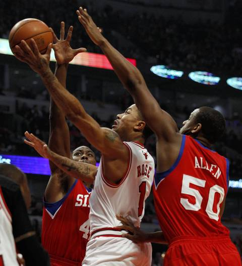 Chicago Bulls point guard Derrick Rose (1) drives to the basket between Philadelphia 76ers power forward Elton Brand (42) and Philadelphia 76ers power forward Lavoy Allen (50) during the first half.