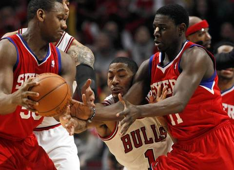Chicago Bulls point guard Derrick Rose (1) tries for the ball between Philadelphia 76ers power forward Lavoy Allen (50) and Philadelphia 76ers point guard Jrue Holiday (11) during the first half