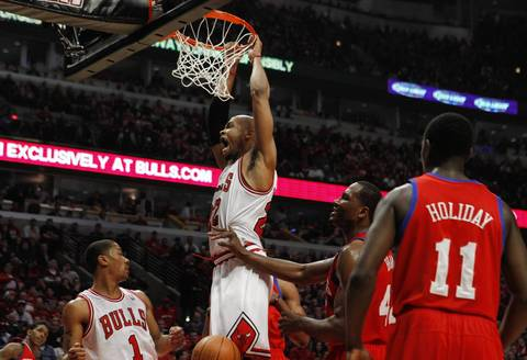 Chicago Bulls forward Taj Gibson (22) hangs on the rim after dunking against the Philadelphia 76ers during the first half.