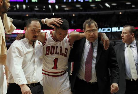 Chicago Bulls point guard Derrick Rose (1) is helped off the court by Chicago Bulls trainers Jeff Tanaka, left, and Fred Tedeschi, right, after he was injured late in the game against the Philadelphia 76ers.
