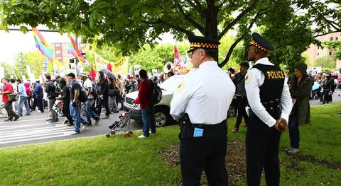 Chicago Police Superintendent Garry McCarthy, white shirt, center, and Al Wysinger, first deputy superintendent, right, watch people march to Federal Plaza from Union Park for May Day.
