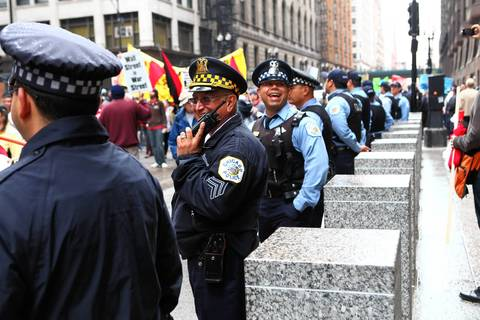 Chicago Police officers stand by as protesters rally in Federal Plaza after marching from Union Park for May Day.