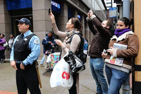 Bystanders document the May Day rally in downtown Chicago.