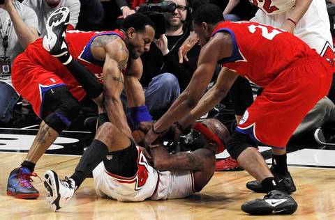 Chicago Bulls shooting guard Richard Hamilton (32) gets his headband in front of his eyes as he's tied up by Philadelphia 76ers Andre Iguodala (left) and Thaddeus Young (21)in the second quarter.