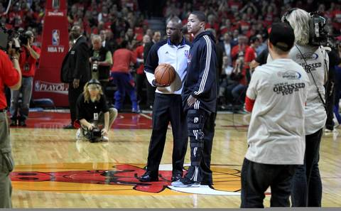 Injured Chicago Bulls point guard Derrick Rose stands at center court while presenting the game ball before the start of game two.