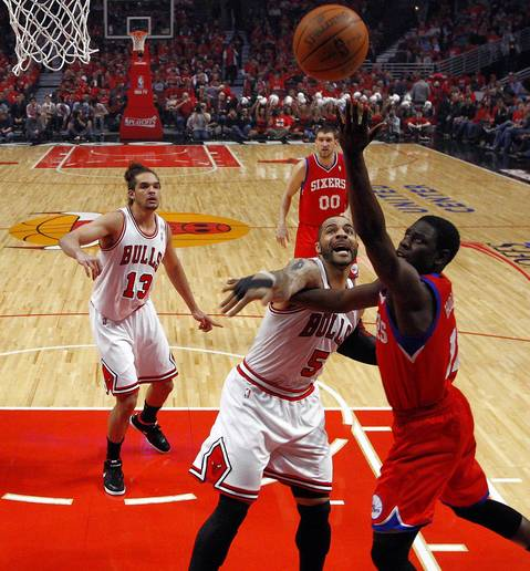 Philadelphia 76ers point guard Jrue Holiday (11) shoots over Chicago Bulls power forward Carlos Boozer (5) during the first quarter.