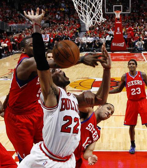 Chicago Bulls forward Taj Gibson (22) has his shot blocked by Philadelphia 76ers power forward Lavoy Allen (50) while being fouled by Evan Turner (12) during the fourth quarter.