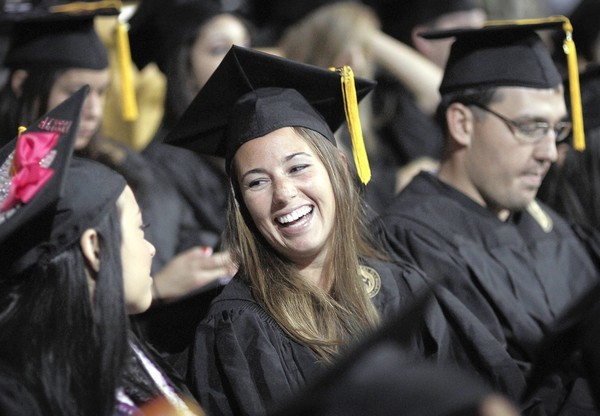 Race-car driver Shea Holbrook sits with fellow graduates as she prepares to walk across the stage at UCF on Saturday.