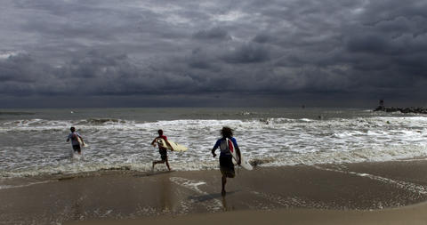 Surfers competing in the Junior Division enter the water to begin their competition as cloudy skies move off shore during the 48th Annual East Coast Surfing Champtionship in Virginia Beach which began on Wednesday and continues through Sunday.