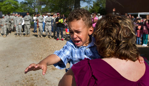 "Elijah Thomas 4, calls ""Dad"" as watches his father Sgt. Dale Thomas board a bus to begin a 12-month deployment to Afghanistan with other soldiers from the 359th Inland Cargo Transfer Company, 6th Transportation Battalion, 7th Sustainment Brigade Monday. Carrying Elijah is his mom Ester Thomas."