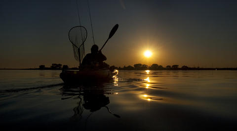 Closing out the day with a sunset paddle back to the boat ramp, Mac McCormick ends an afternoon of fishing on Back River with his wife Ruth McCormick Monday.