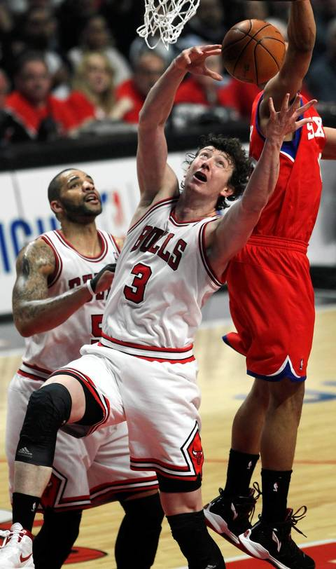 Chicago Bulls center Omer Asik tries to grab a rebound in front of Philadelphia 76ers shooting guard Evan Turner in the first quarter of game at the United Center.