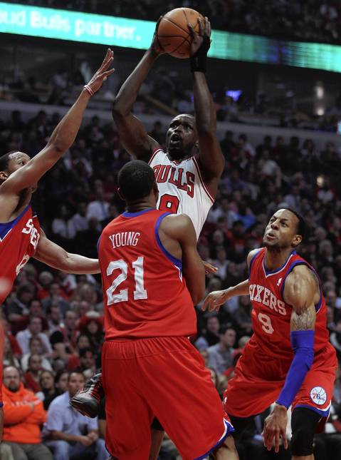 Chicago Bulls small forward Luol Deng shoots over Philadelphia 76ers forward Thaddeus Young in the first quarter at the United Center.