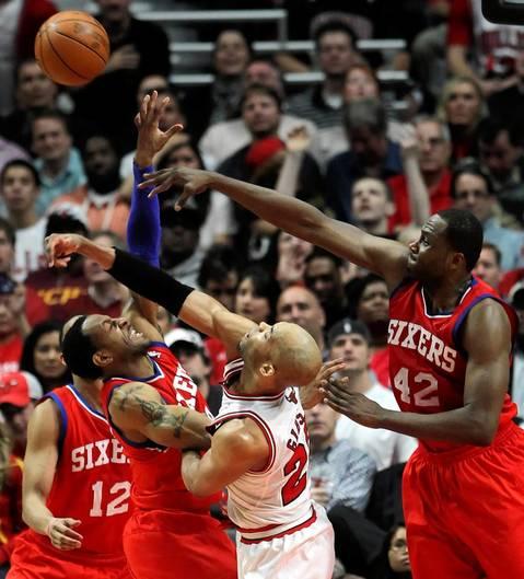 Chicago Bulls forward Taj Gibson battles Philadelphia 76ers small forward Andre Iguodala (left) and Philadelphia 76ers power forward Elton Brand (right) for a rebound in the second quarter at the United Center.