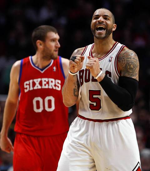 Chicago Bulls power forward Carlos Boozer yells in front of Philadelphia 76ers center Spencer Hawes in the fourth quarter in as the Bulls win Game 5 at the United Center.