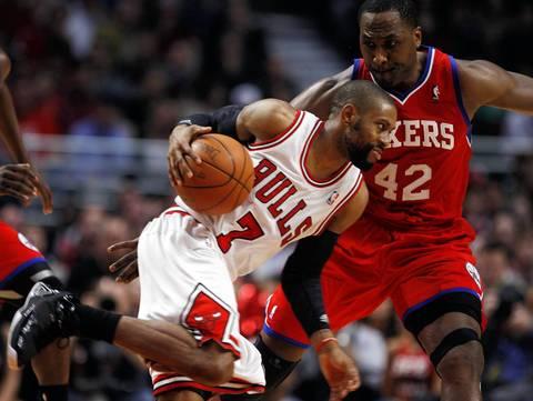 Chicago Bulls point guard C.J. Watson goes against Philadelphia 76ers power forward Elton Brand at the United Center.