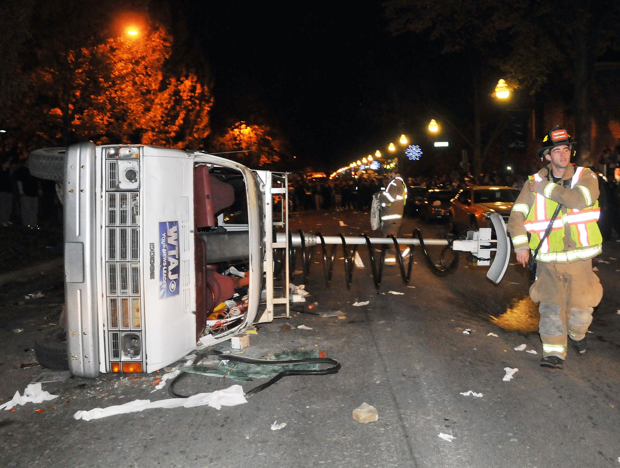 An overturned news van is seen in the middle of College Ave as students protest against the firing of Penn State football coach Joe Paterno in State College, Pennsylvania.