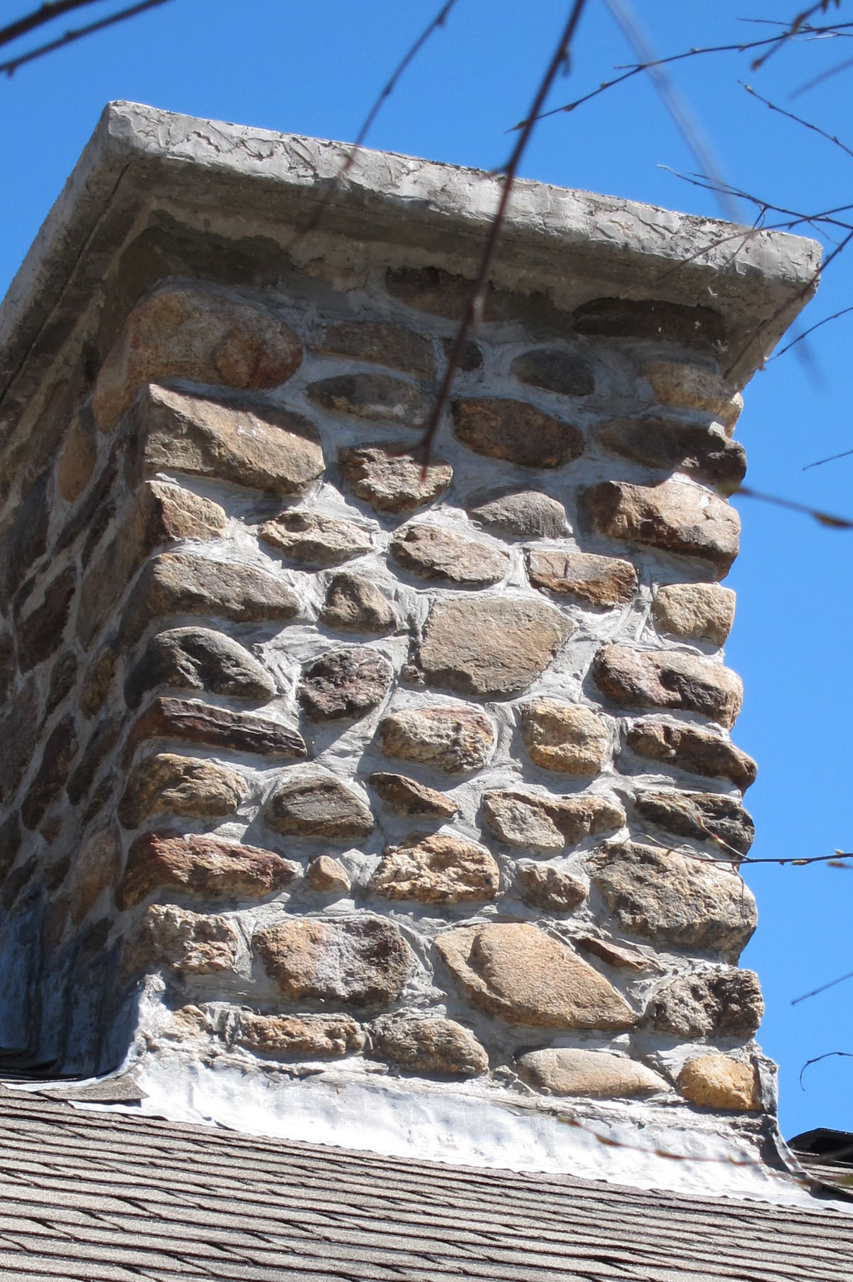 This stone chimney has a properly constructed top or crown. You can even see the drip groove under the overhang.