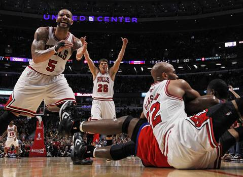 Carlos Boozer and Kyle Korver yell as Chicago Bulls forward Taj Gibson and Philadelphia 76ers power forward Elton Brand fight for the ball in the second quarter at the United Center.