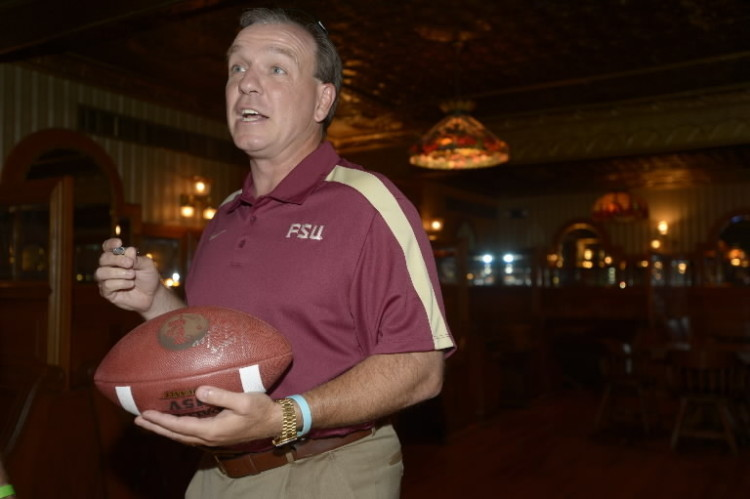 Florida State University head football coach Jimbo Fisher autographs a football for a fan during a booster club event in Orlando, Fla., Saturday, May 12, 2012. (Photo by Phelan M. Ebenhack for the Orlando Sentinel)