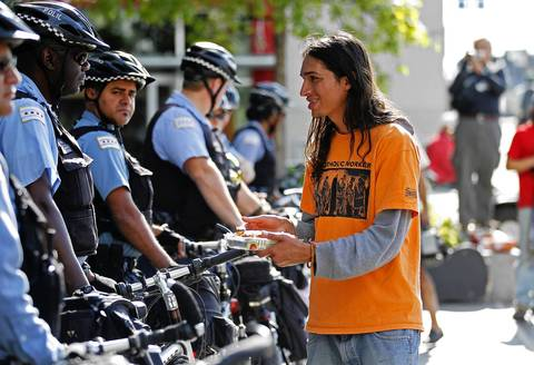 Robert Majors, with Catholic Workers, offers a pastry to Chicago police officers outside of the Prudential Building.