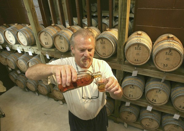 Dick Waters samples the finished whiskey from his still at his farm near Umatilla.