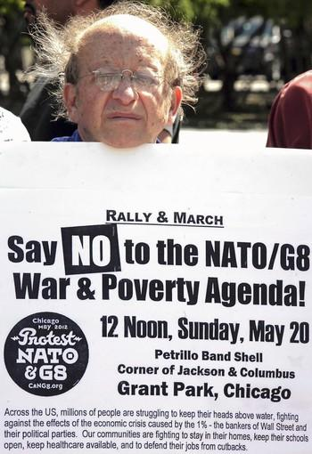 Marty Goodman holds up his signage as the group, Coalition Against NATO/G8 War and Poverty, hold a press conference outside the Hyatt Regency Hotel at McCormick Place.