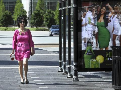 Nancy Mancias, of San Francisco, sports a pink dress with signage as she arrives with the group Coalition Against NATO/G8 War and Poverty, before a press conference outside the Hyatt Regency Hotel at McCormick Place.