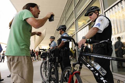 An Occupy Chicago protester yells at Chicago Police Department's Sergeant Walsh during immigration detention rally at Immigration Court Building in Chicago.