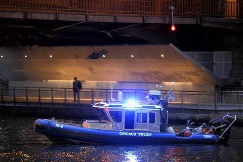 A Chicago police boat helps block traffic on the Chicago River near the Michigan Avenue Bridge as a person walks past on the River Walk path.